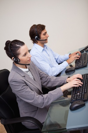 Side view of young call center agents at work photo