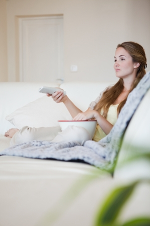 woman watching tv: Young woman on the sofa enjoying a movie with popcorn Stock Photo