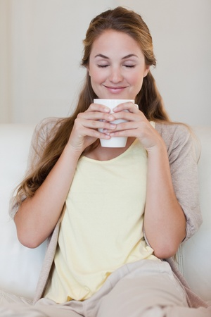 Young woman enjoys smelling on her fresh made coffee photo