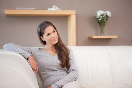 unbend: Young woman sitting on the sofa
