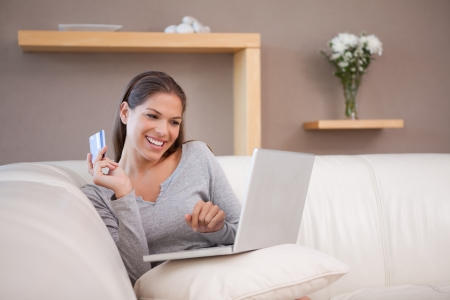 Young woman shopping online on her sofa photo
