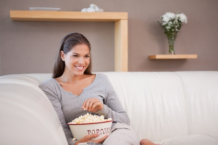 Smiling young woman having popcorn while watching a movie photo
