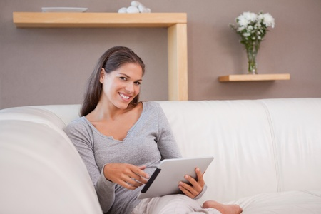 Young woman with tablet pc on the couch photo