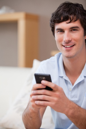 Smiling young man with cellphone in his hands photo