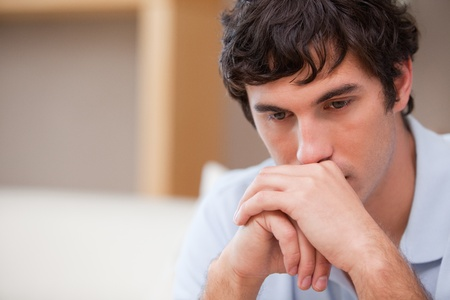 man couch: Thoughtful young man in the living room Stock Photo