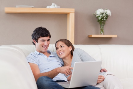 Young couple with their notebook on the sofa photo