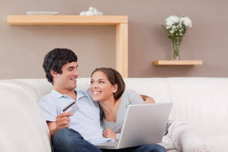 Cheerful young couple booking holiday online photo