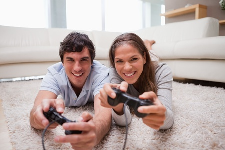 game room: Young couple playing video games in the living room Stock Photo