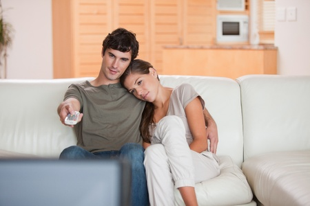 Young couple on the sofa watching television together photo