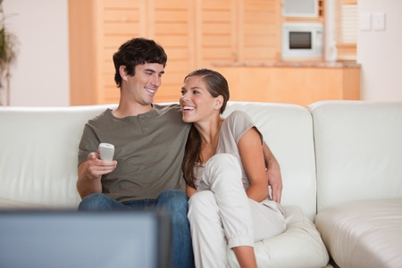Laughing young couple watching funny movie together photo