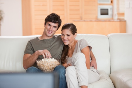 Young couple with popcorn on the sofa watching a movie photo