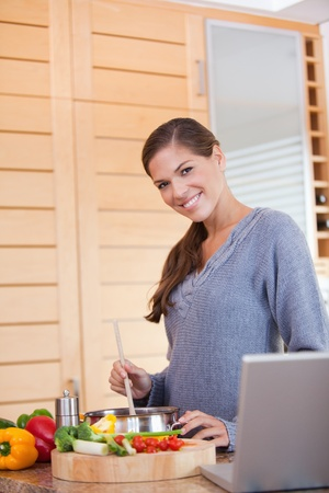 Smiling young woman stirring the meal she is preparing photo