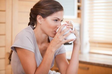 tomando café: Vista lateral de café para beber joven mujer