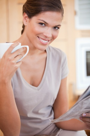 Smiling young woman reading the news while drinking coffee photo