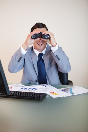 Smiling businessman at his desk looking through binoculars photo