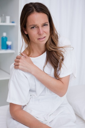 Woman covering painful shoulder with her hand photo