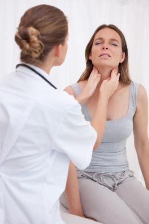 Doctor examining patients painful throat photo