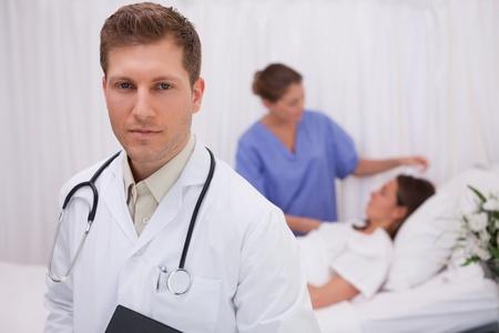 Doctor standing in his patients room with patient and\ colleague behind him