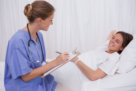 Surgeon talking with bedridden patient photo