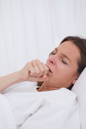 couching: Woman lying in bed while couching Stock Photo