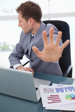 Businessman at his desk does not want to listen photo