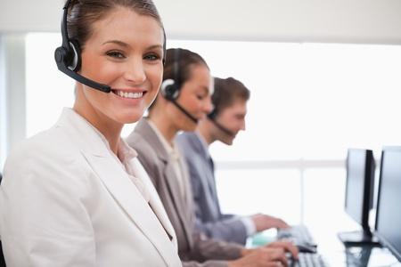 call center agent: Sorridente centro call agent con i colleghi di lavoro alle spalle