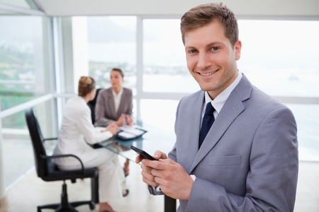 Sales manager holding cellphone with his team sitting behind him photo