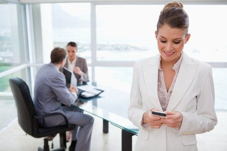 conference call: Marketing manager reading text message with her team sitting behind her Stock Photo