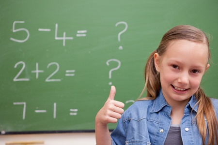 Schoolgirl with the thumb up in front of a blackboard Stock Photo - 11679610