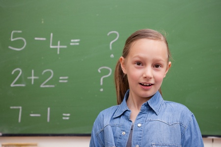 Smiling schoolgirl posing in front of a blackboard Stock Photo - 11679606