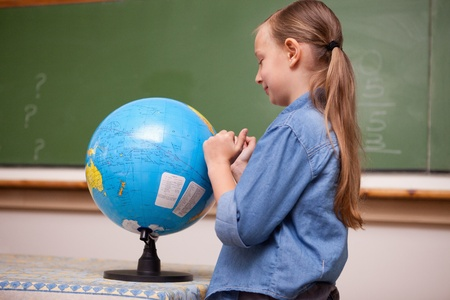 Schoolgirl looking at a globe in a classroom photo