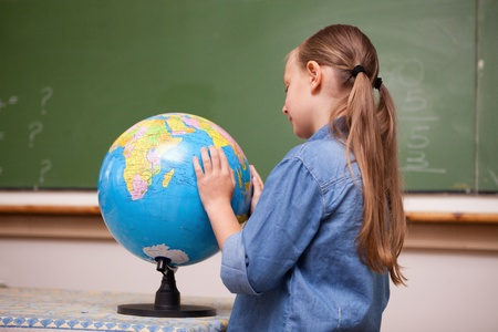 schoolkid search: Focused schoolgirl looking at a globe in a classroom