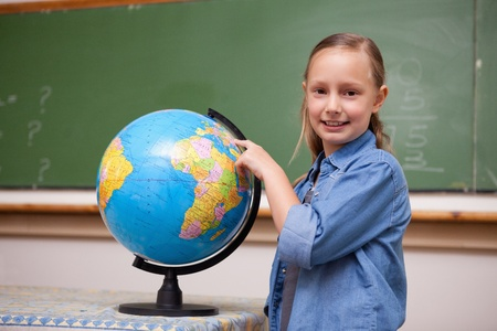 Smiling schoolgirl looking at a globe in a classroom photo