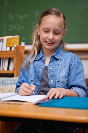 Portrait of a happy schoolgirl writing in a classroom Stock Photo - 11679670