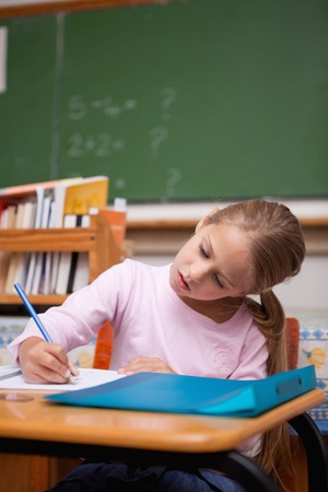 Portrait of a focused schoolgirl writing in a classroom Stock Photo - 11679720