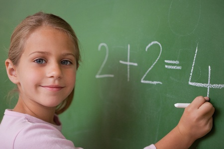 Smiling schoolgirl writing a number in a blackboard Stock Photo - 11679578