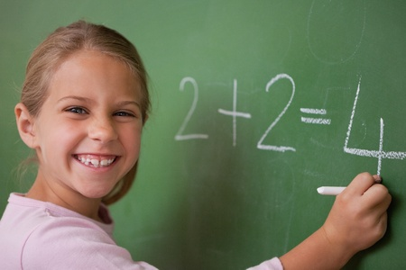 Happy schoolgirl writing a number on a blackboard photo