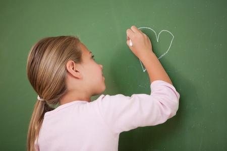 Schoolgirl drawing a heart on a blackboard photo