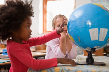 preschool classroom: Happy schoolgirls looking at a globe in a classroom