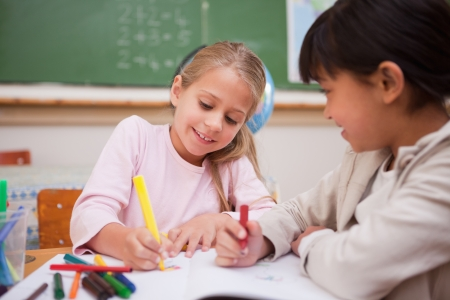 primary colours: Smiling schoolgirls drawing in a classroom Stock Photo
