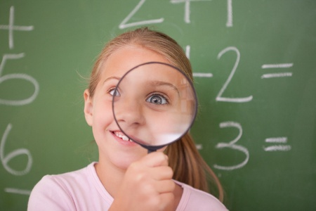 schoolkid search: Playful schoolgirl looking through a magnifying glass in a classroom Stock Photo