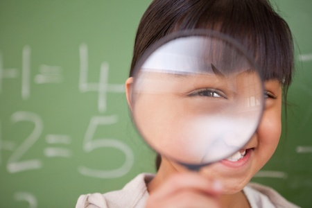 schoolkid search: Close up of a cute schoolgirl looking through a magnifying glass in a classroom