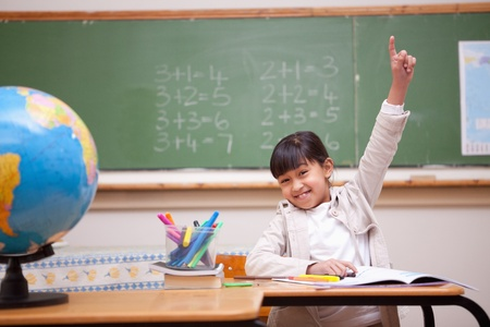 raise hand: Schoolgirl raising her hand to answer a question in a classroom Stock Photo