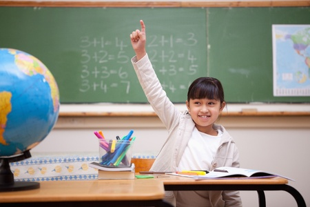 Smiling schoolgirl raising her hand to answer a question in a classroom photo