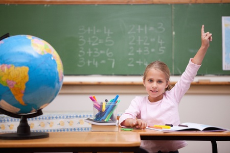 Cute schoolgirl raising her hand to answer a question in a classroom photo