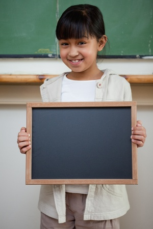 Portrait of a girl holding a school slate in a classroom photo