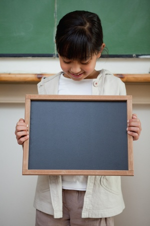 Portrait of a cute girl holding a school slate in a classroom photo