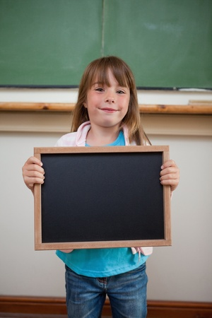 Portrait of a smiling girl holding a school slate in a classroom photo
