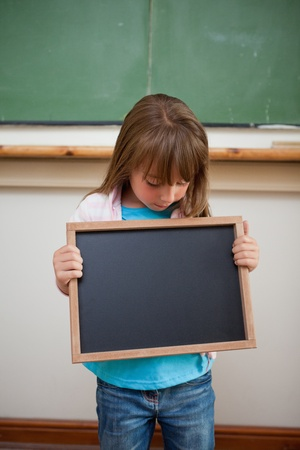 Portrait of a girl looking at a school slate in a classroom photo