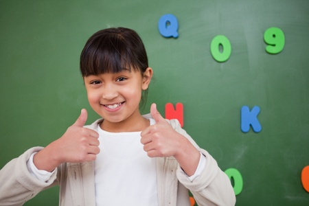 Happy schoolgirl with the thumbs up in front of a blackboard photo